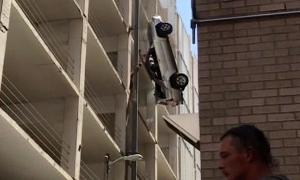 Автомобиль вылетел высотной парковки и повис на проводах (Видео)